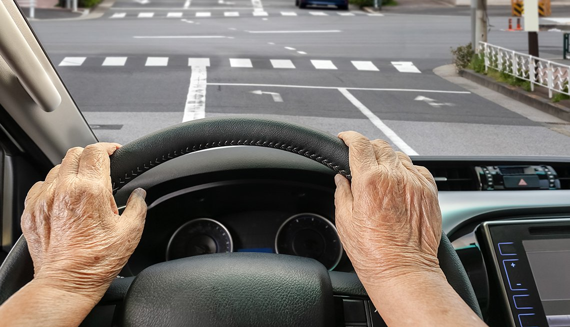 older woman driving on a city street