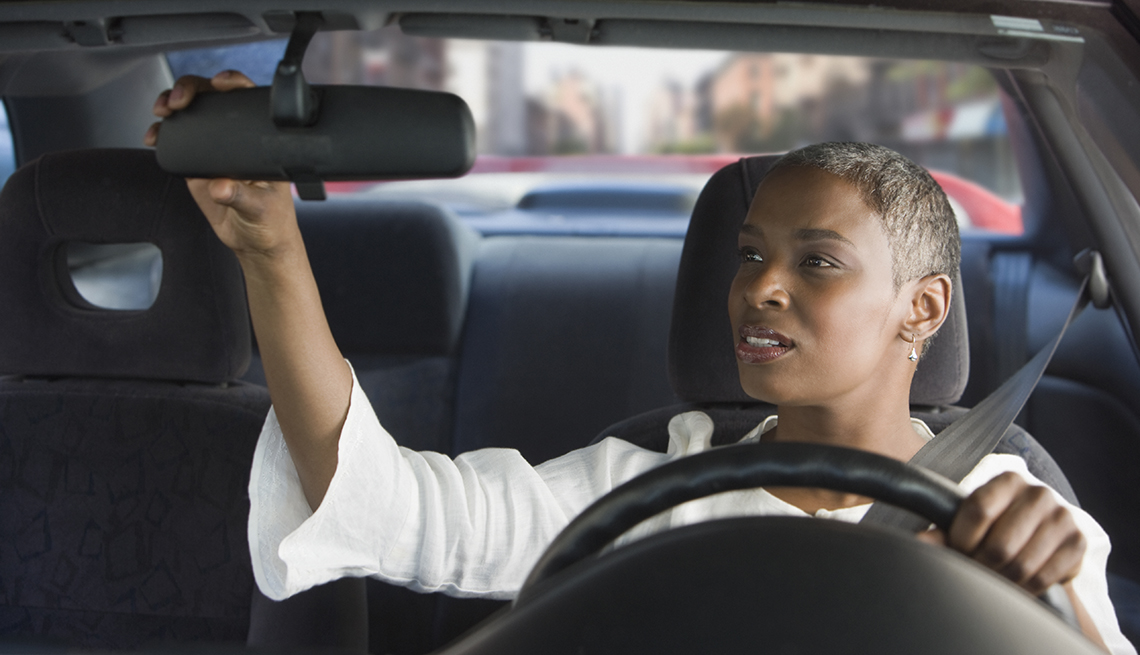 woman adjusting rear view mirror