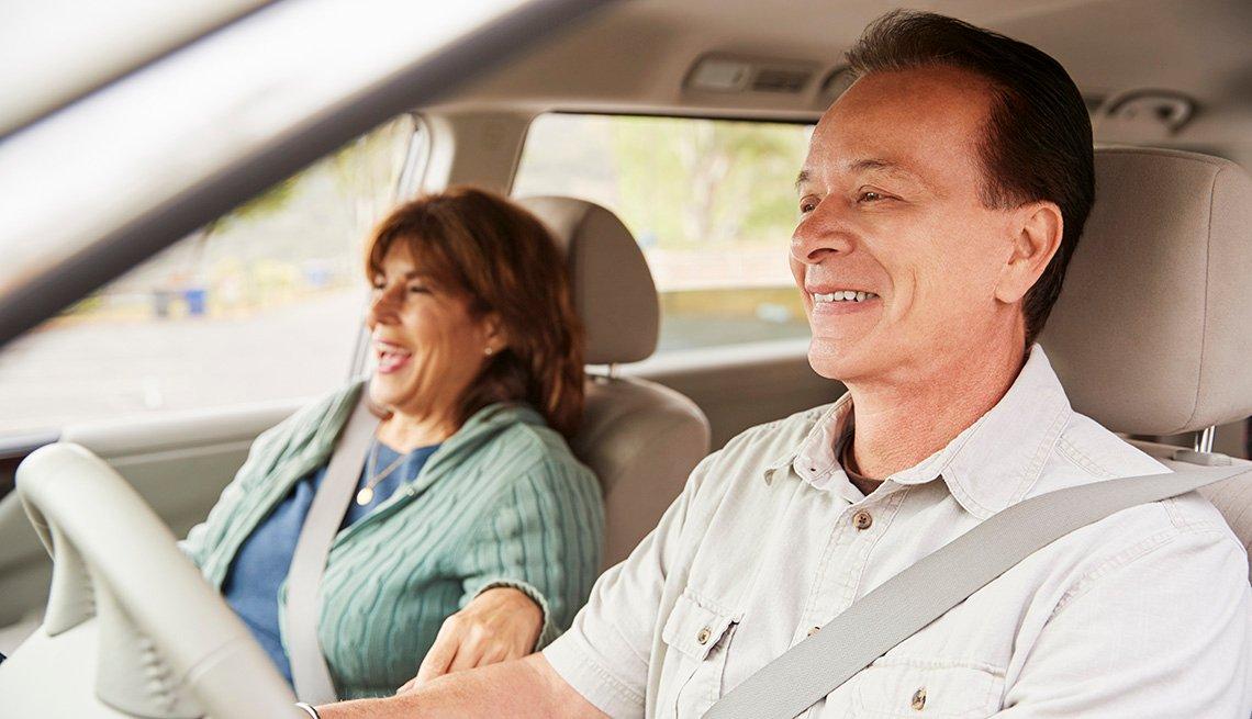 Un hombre y una mujer sonríen dentro de un automóvil