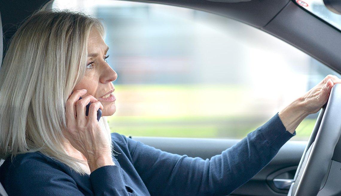 Mujer habla por teléfono mientras conduce un automóvil