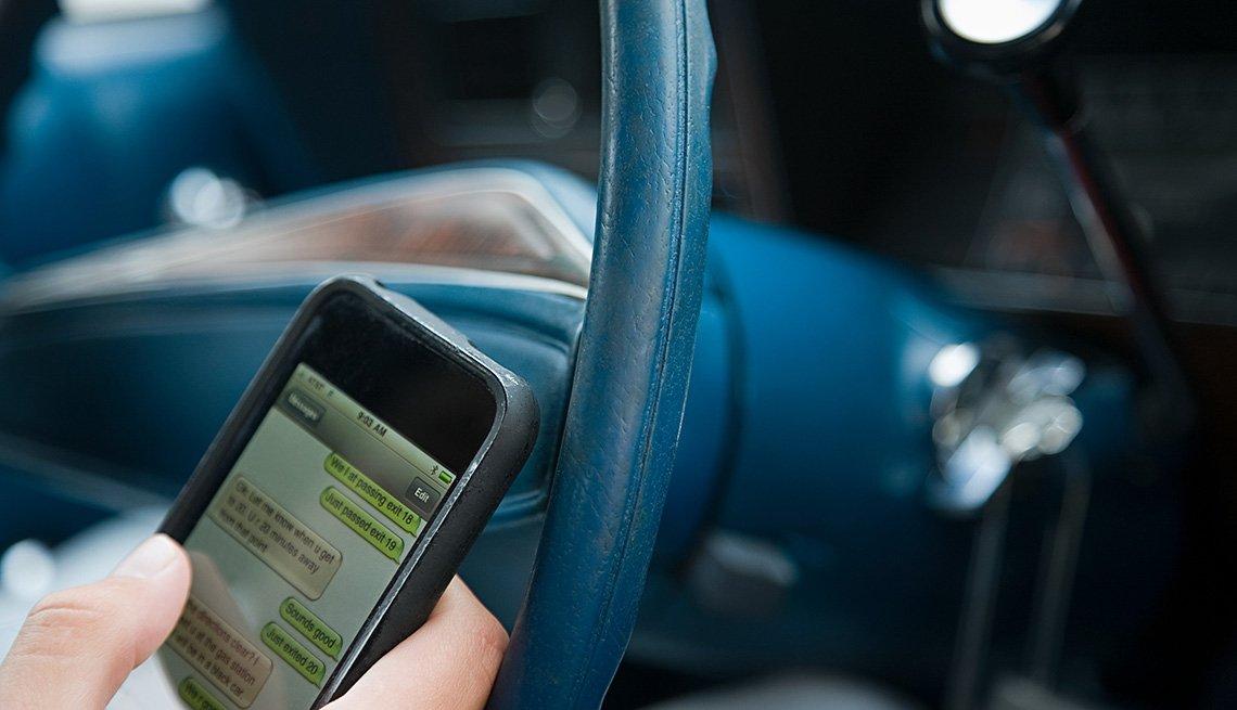 Persona escribe en su teléfono móvil mientras conduce