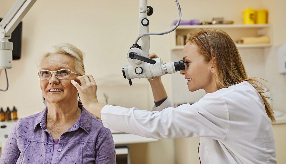 Médica examina el oído de una mujer