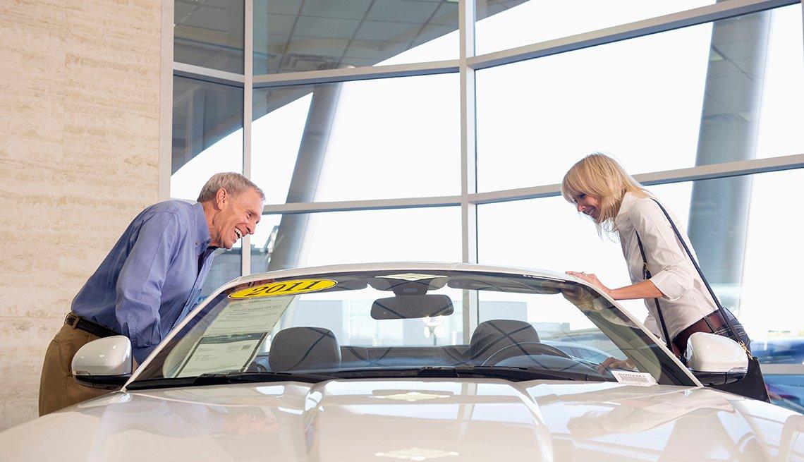 couple admiring car in dealership