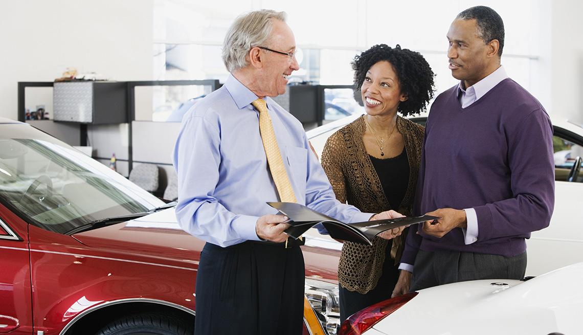 Una pareja que busca comprar un automóvil habla con un vendedor