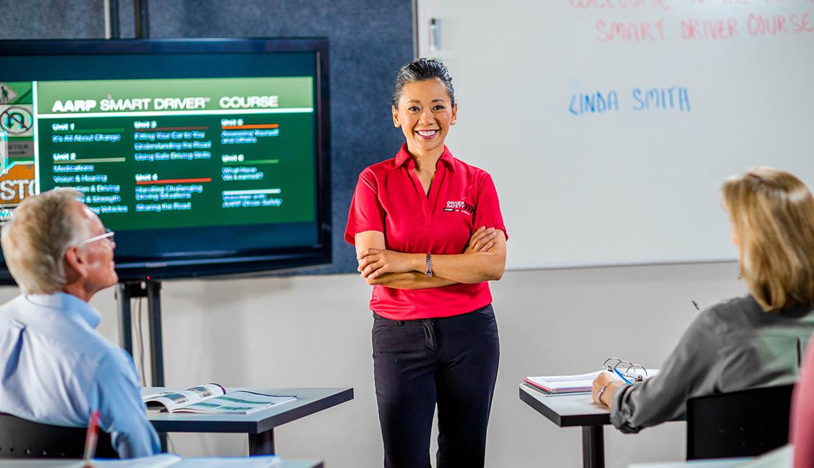 Instructora voluntaria de AARP Smart Driver en un aula junto a dos personas