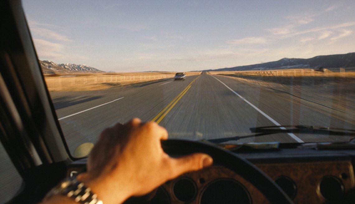 Mano de un hombre en el volante de un vehículo