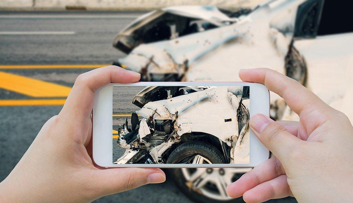 Mujer toma una foto con un teléfono inteligente de un accidente automovilístico en la carretera