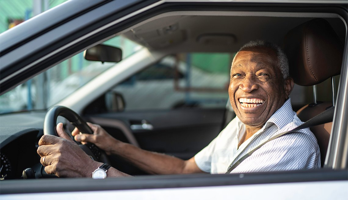 Smiling man driving a car and looking at camera