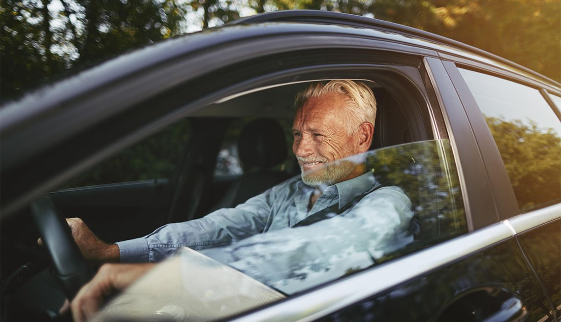 man smiling while sitting alone in his car enjoying a drive on a road in the countryside