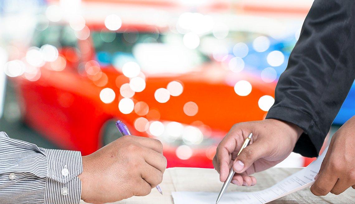 Hombre firma el documento de arrendamiento de su auto
