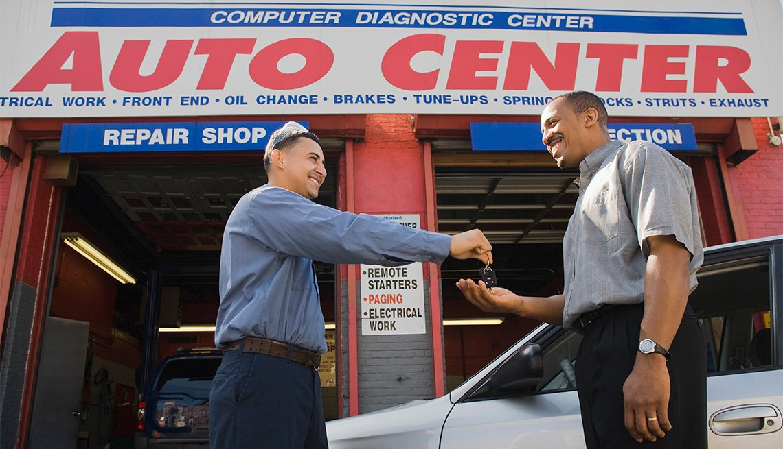 Mechanic giving customer his car keys at auto shop
