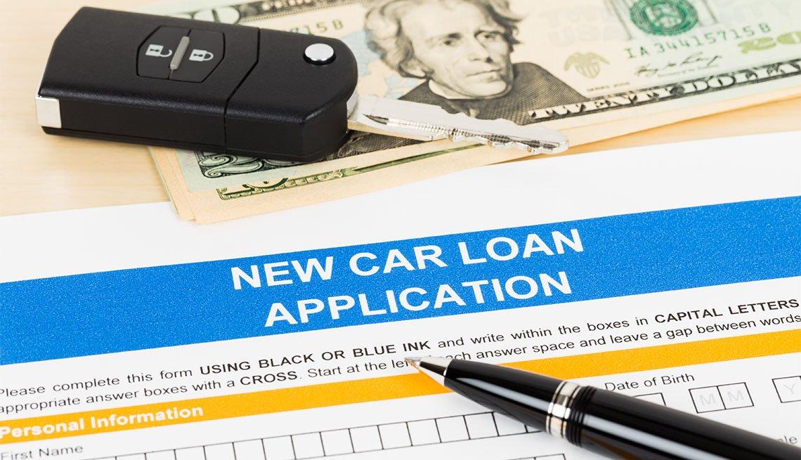Solicitud de préstamo para comprar un auto y una llave de vehículo sobre un billete de 20 dólares