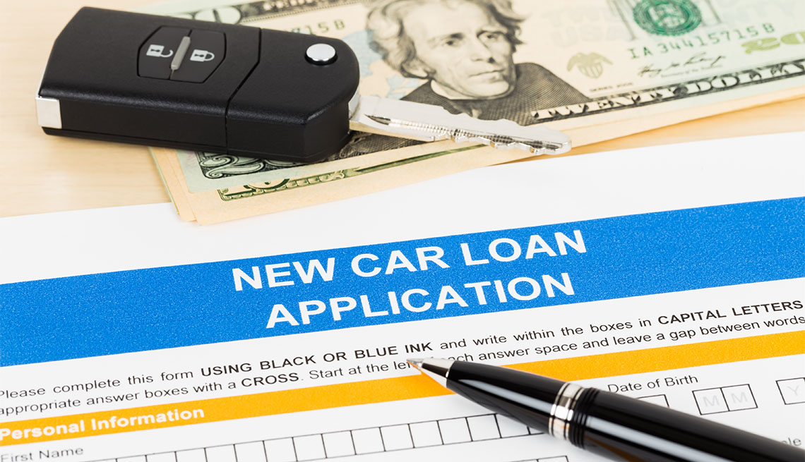 Car loan application with car key and dollar banknote
