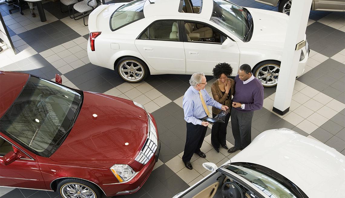 Pareja hablando con un vendedor en un concesionario de automóviles