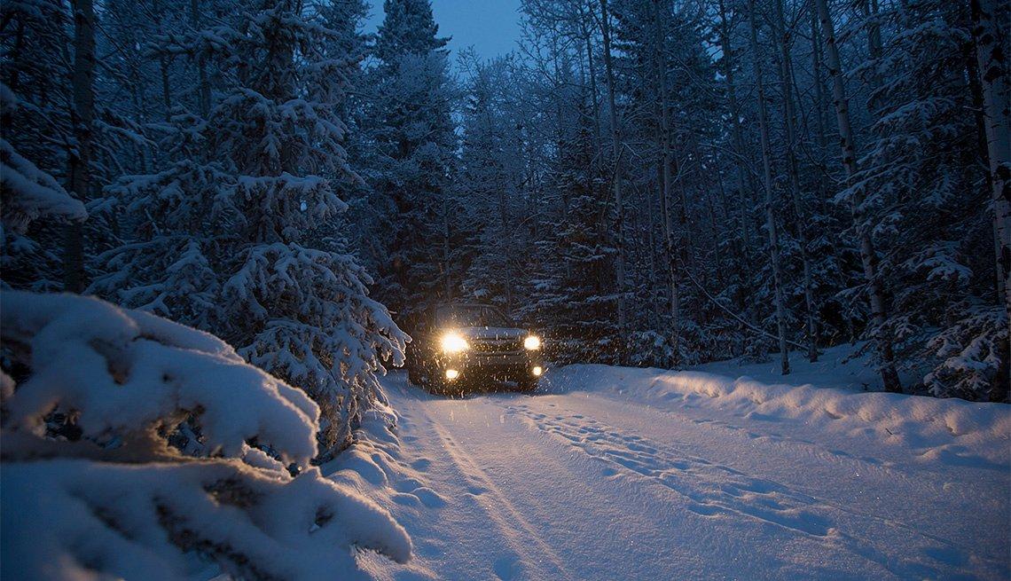 Auto conduce en la carretera cubierta de nieve entre las montañas