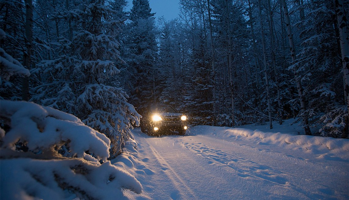 car driving on snow covered road at night
