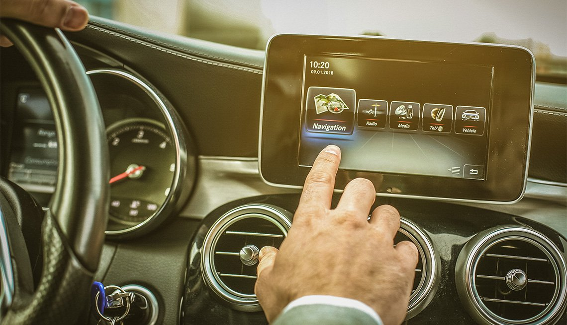 Close up of driver hand using touch screen in car