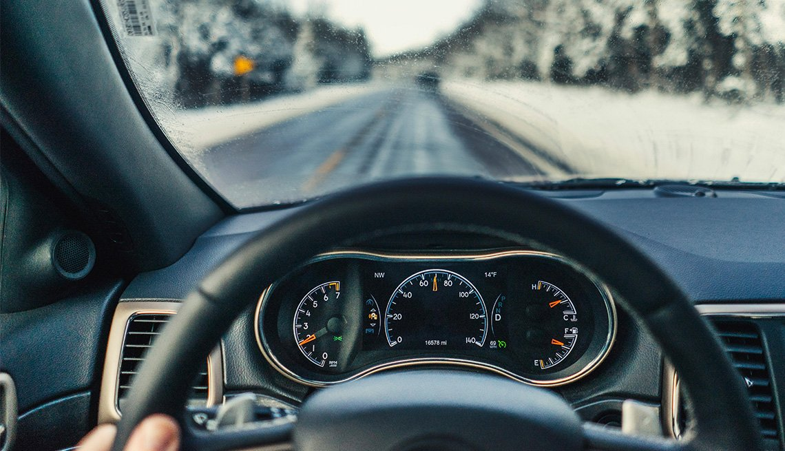 fingers of man driving car on road during winter