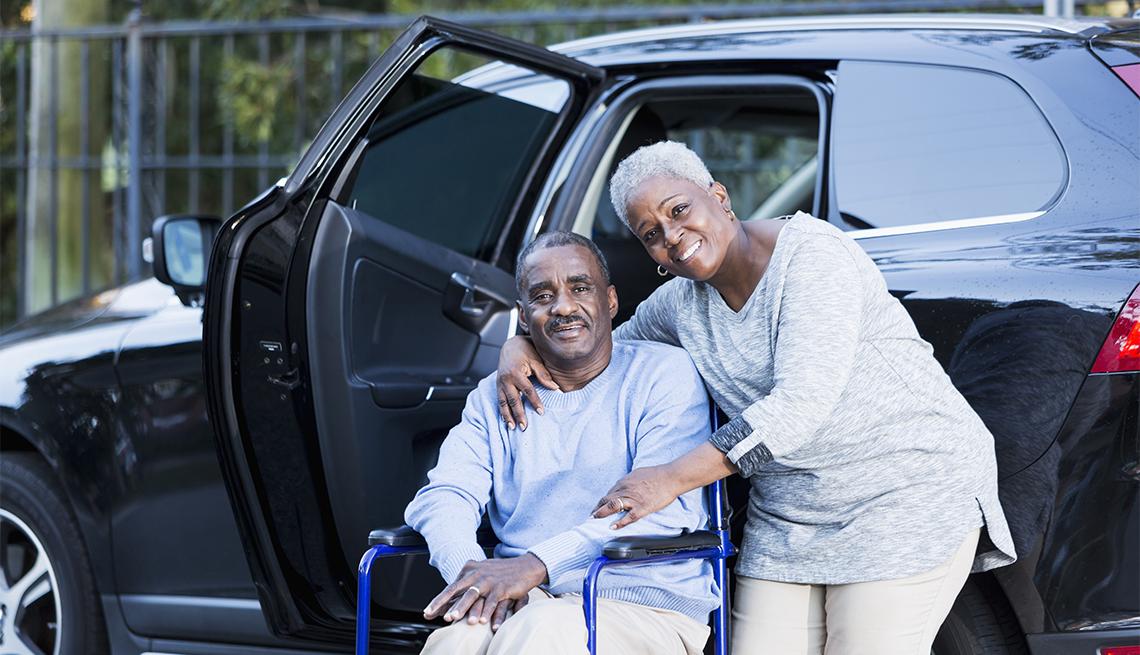 Un hombre discapacitado sentado en una silla de ruedas junto a su esposa y al lado de su automóvil