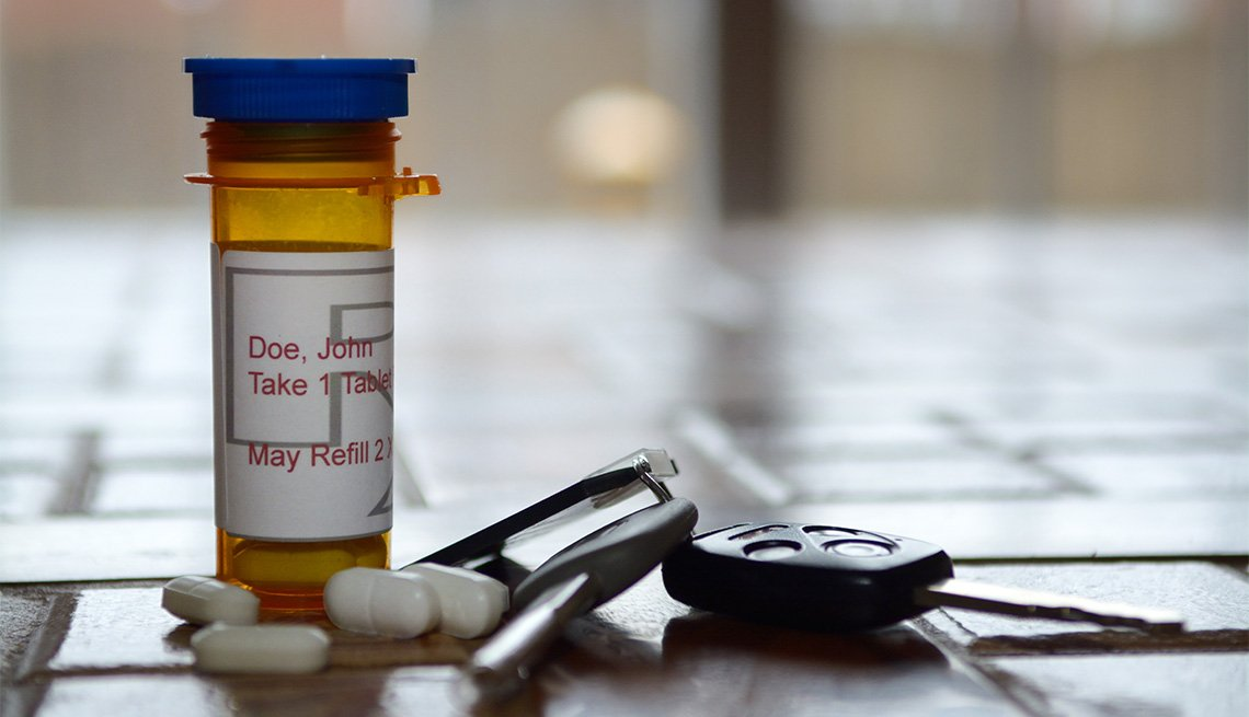 Frasco de medicinas junto a algunas pastillas y las llaves de un auto
