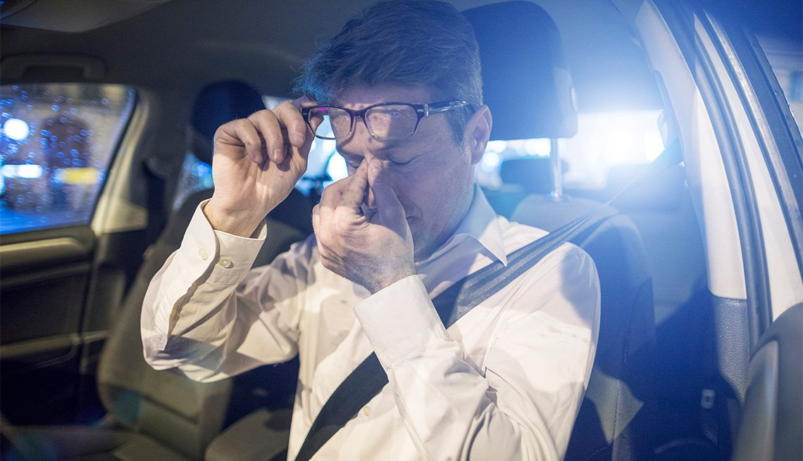 Tired male driver inside car at night