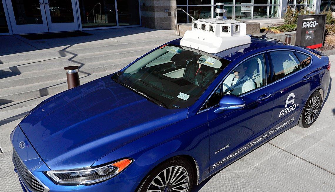 Un auto azúl sin conductor, con cámaras y sensores en el techo