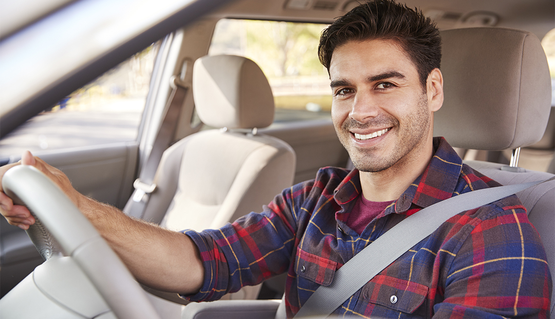 Young man in car driving seat looking to camera