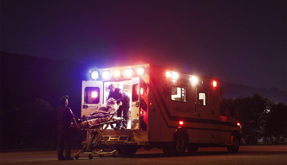 Trabajadores de servicios médicos de emergencia suben un paciente a una ambulancia