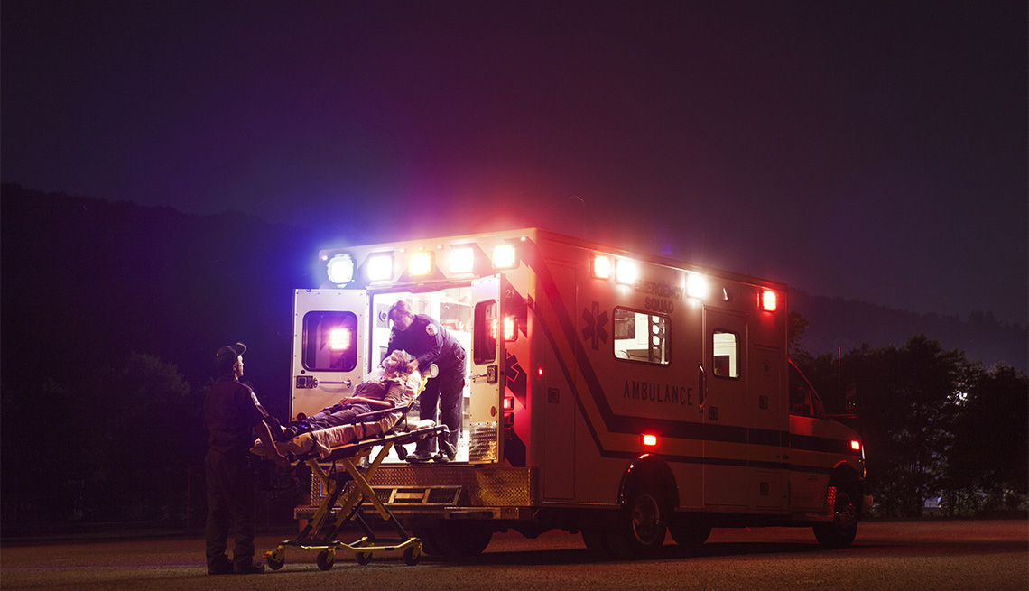 Emergency medical services workers putting putting a patient in an ambulance
