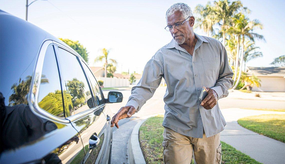 Un hombre mayor se sube a un auto