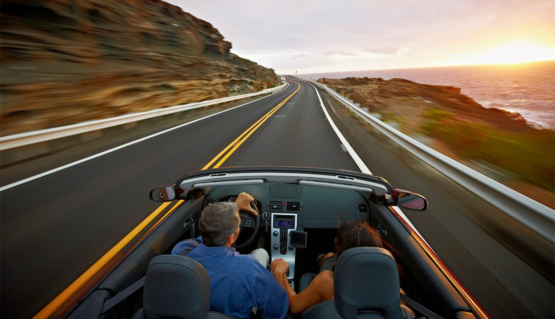 Husband and wife driving convertible along coastal road at sunrise