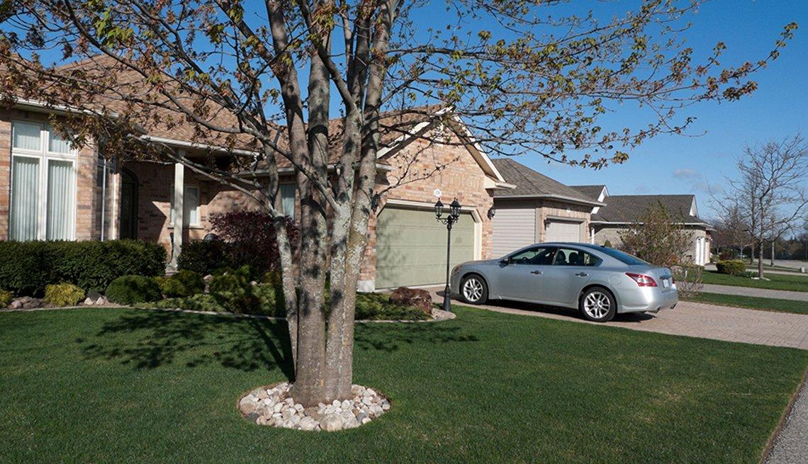 Casa con un auto gris parqueado frente a su casa