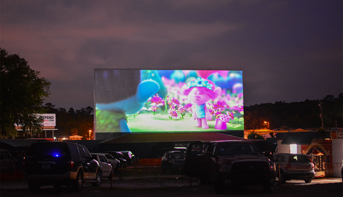 People watch the movie Trolls from their cars, separated from other cars by a 10-foot orange fencing in an effort to respect social distancing amid the novel coronavirus pandemic, at the Ocala drive-in theatre in Ocala, Florida on April 25, 2020