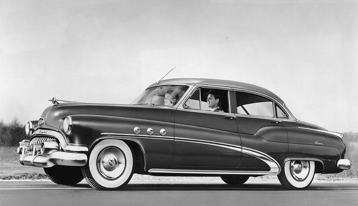 couple driving a 1952 Buick Super Riviera four-door Sedan