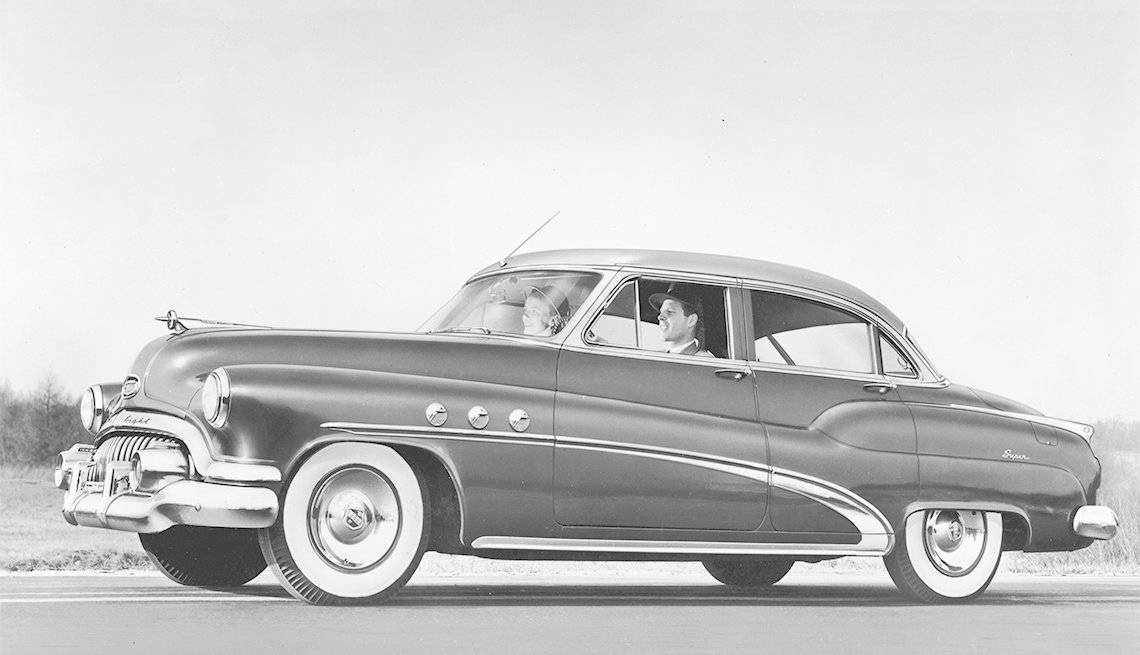 couple driving a 1952 Buick Super Riviera four-door Sedan