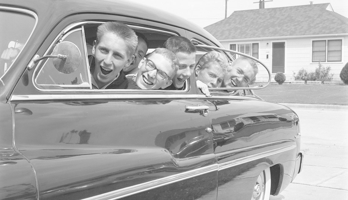 black and white photo taken in the nineteen fifties or sixties of five teenage boys all smiling and laughing peeking out the windows of their car