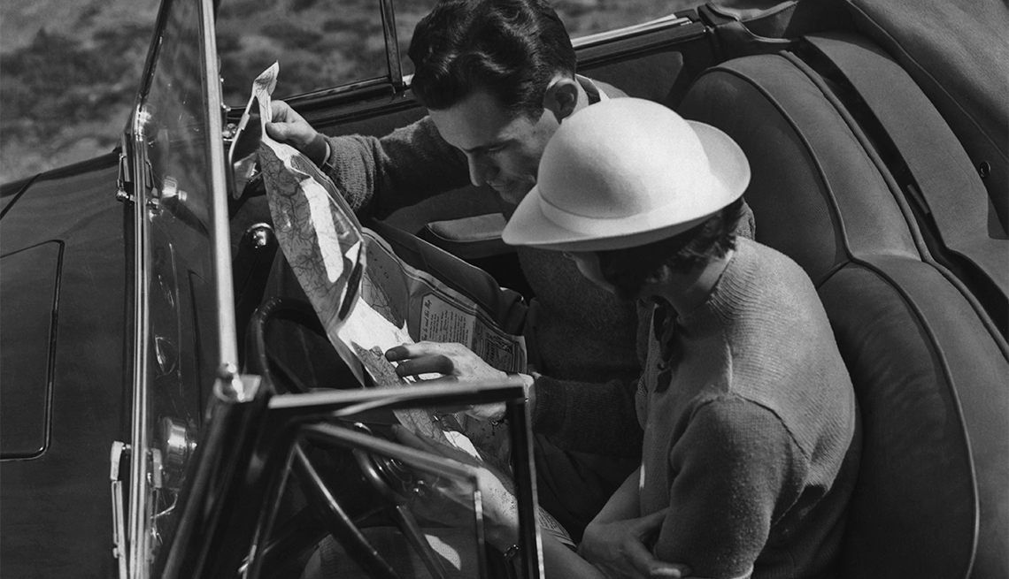 item 7 of Gallery image - A couple checking a road map in a convertible car circa 1950