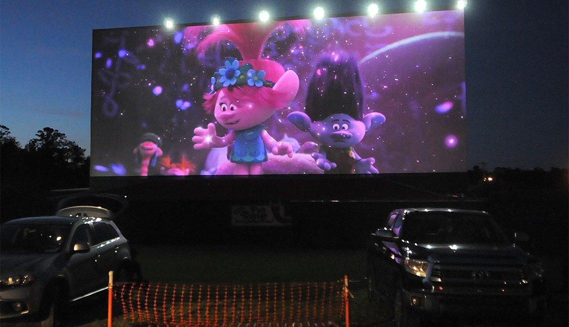 Autos parqueados frente a una pantalla de cine
