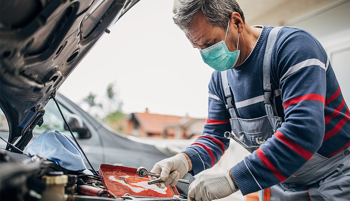 mechanic wears a mask while working on a car