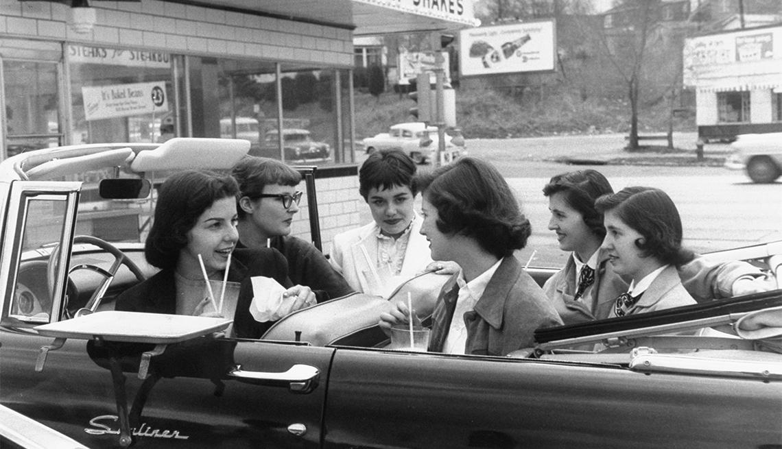 item 1 of Gallery image - Teenage girls enjoying 29 cent milkshakes at drive-in restaurant