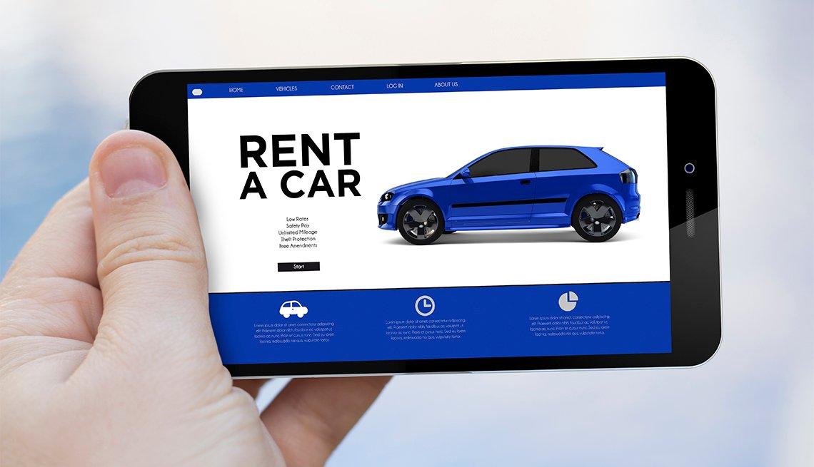 Mano sosteniendo un teléfono con una aplicación de alquiler de autos