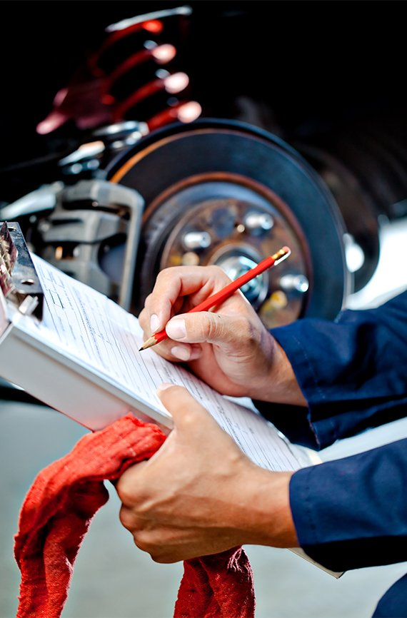 mechanic writing an auto estimate for repair work