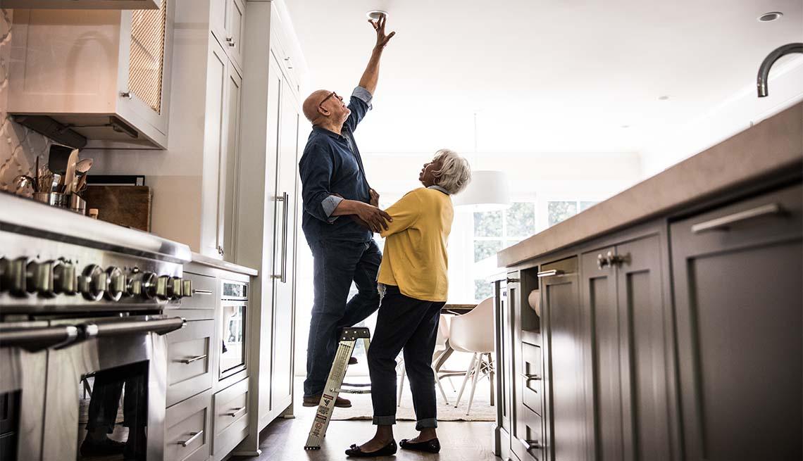 Una pareja de adultos mayores hace arreglos en la casa