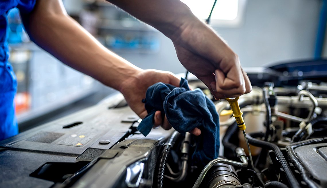 Photo of male mechanic measuring the oil level of an engine at an auto shop