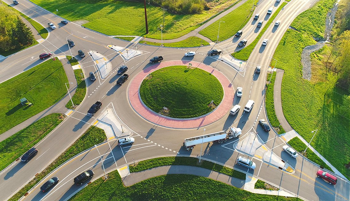 aerial view of a busy city roundabout intersection at sunrise rush hour