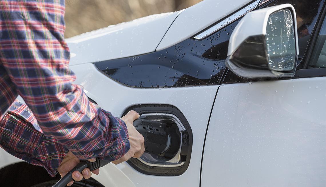 Hombre conectando un auto eléctrico a la estación de carga