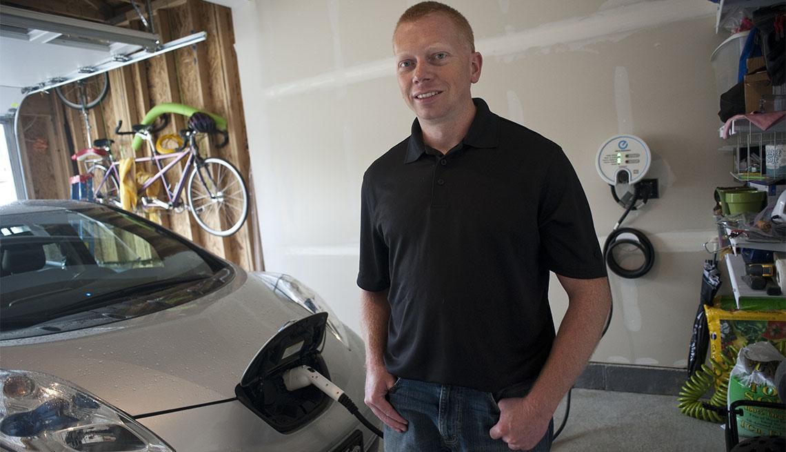 Tim Edmonson posa para una foto junto a la estación de carga de su auto eléctrico
