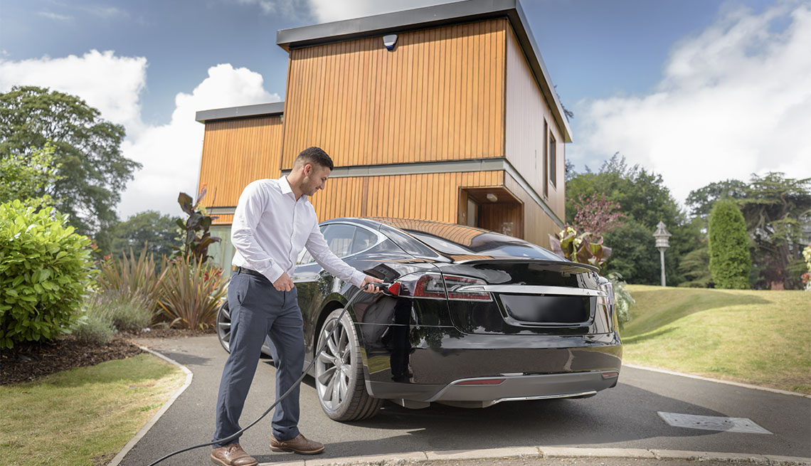 man charging electric car at home