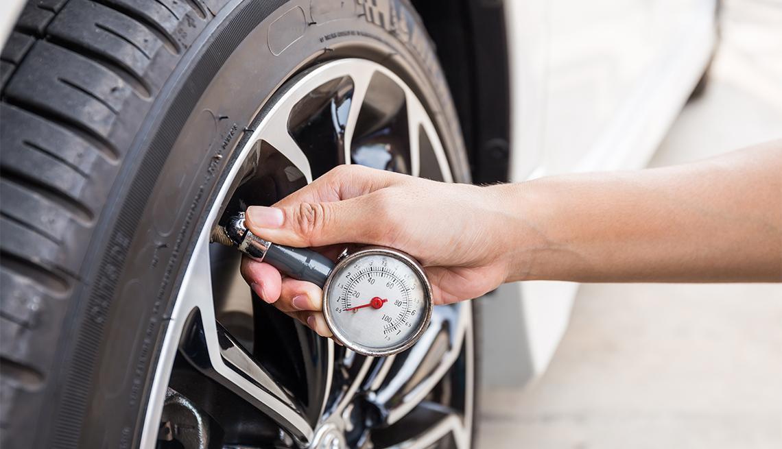 Persona revisa el nivel de presión de las llantas de su auto