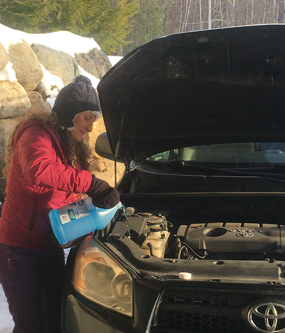 woman adding engine fluid to her Toyota